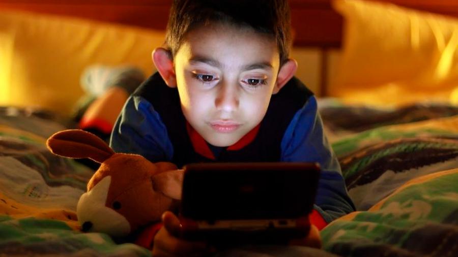 Medio centenar de estudios coinciden: los niños que miran una pantalla antes de acostarse tienden a dormir menos (y engordan más)