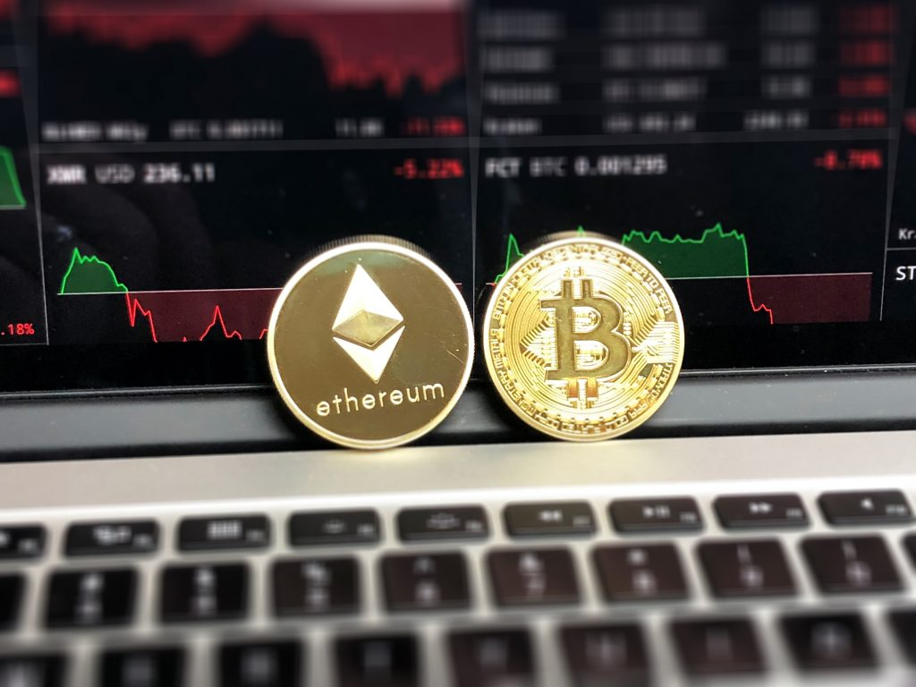 monedas de bitcoin y ethereum frente a una pantalla con gráficos